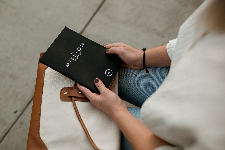 """Eine Frau hält ein Buch mit der Aufschrift """"The Mission Journal"""" in den Händen."""
