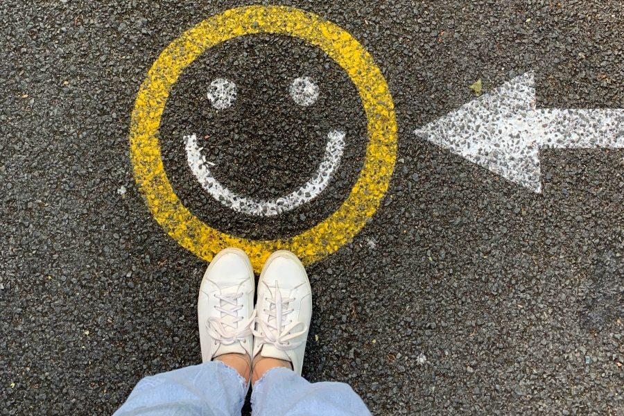 Eine Person, von der nur die Beine zu sehen sind, blickt von oben auf einen Smile, der mit Kreide auf die Straße gezeichnet ist. Ein Pfeil zeigt von rechts auf den Smile.