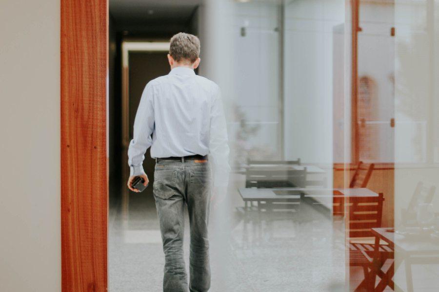 Rückansicht eines Mannes, der einen Raum verlässt.