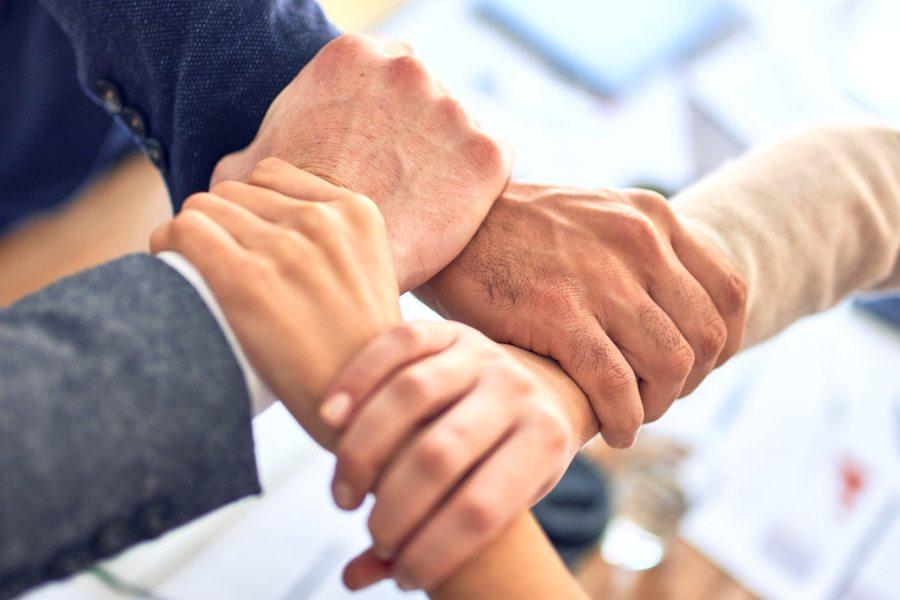 Hände von vier Personen greifen ineinander als Zeichen für ein Team.