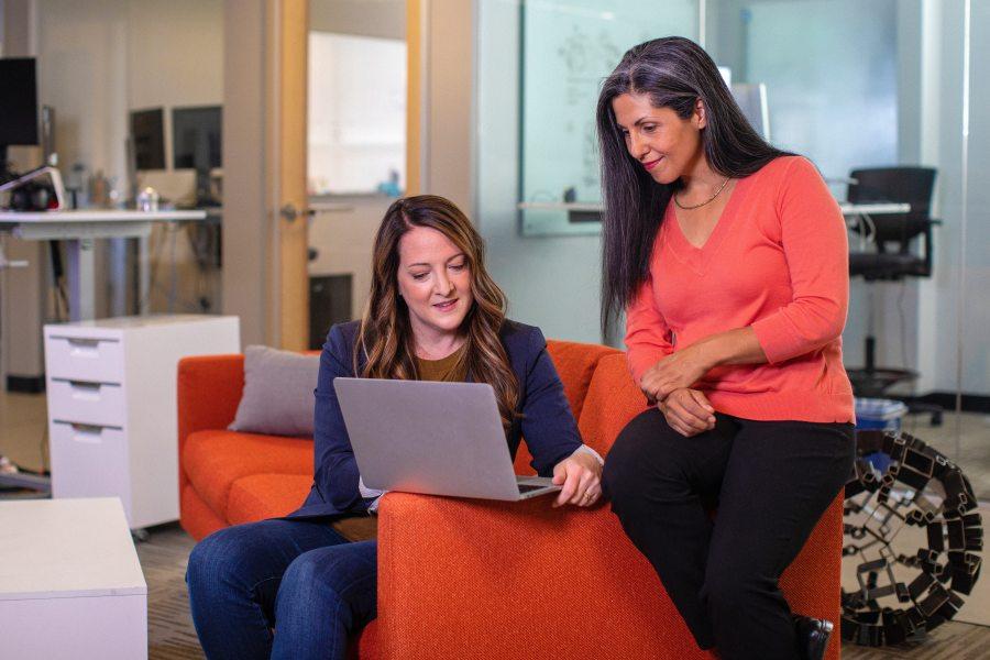Zwei Frauen sitzen auf einem roten Sofa in einem Büro. Die jüngere der beiden zeigt der älteren etwas auf einem Laptop.