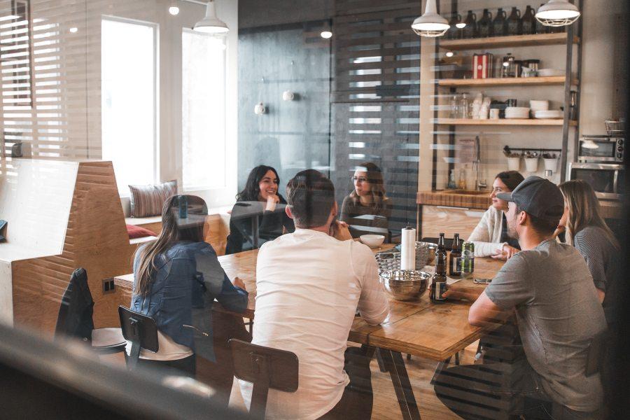 Eine Gruppe junger Menschen unterhält sich an einem Tisch im Büro.